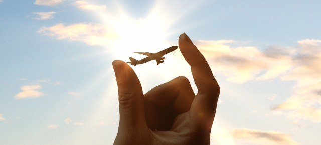 hand-holding-airplane-on-sky-background-1444148483-i8Ao-slide