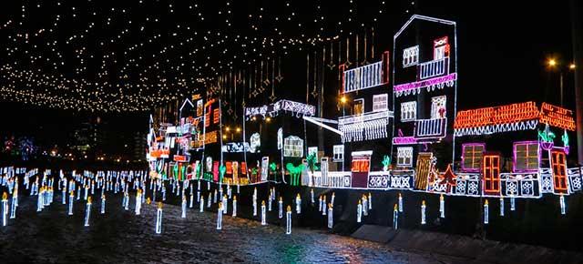 Foto nocturna de una ciudad junto al mar decorada por Navidad